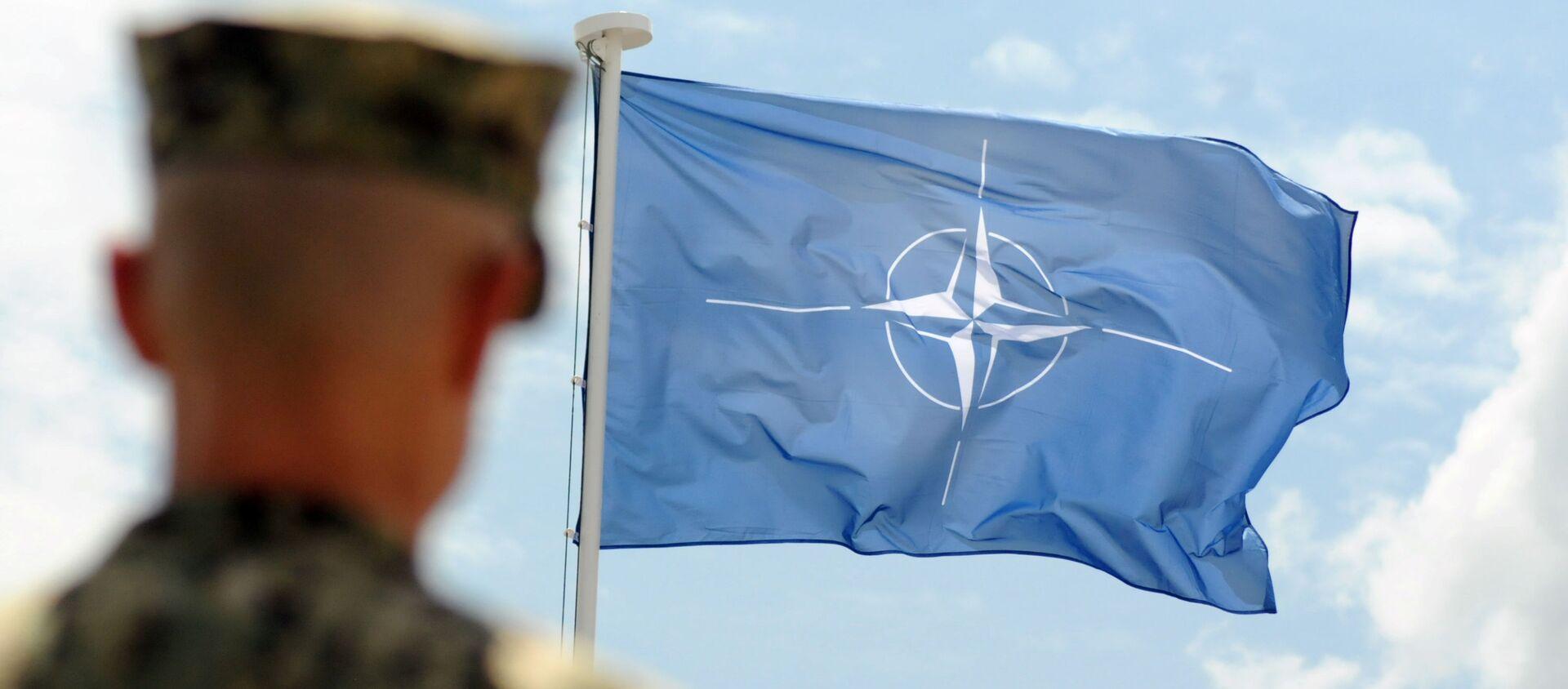 Военнослужащий НАТО на фоне флага НАТО в Косово - Sputnik 日本, 1920, 01.07.2021