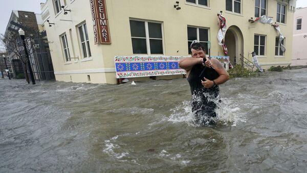 9月16日、米フロリダ州ペンサコーラで、冠水した街を歩く男性 - Sputnik 日本