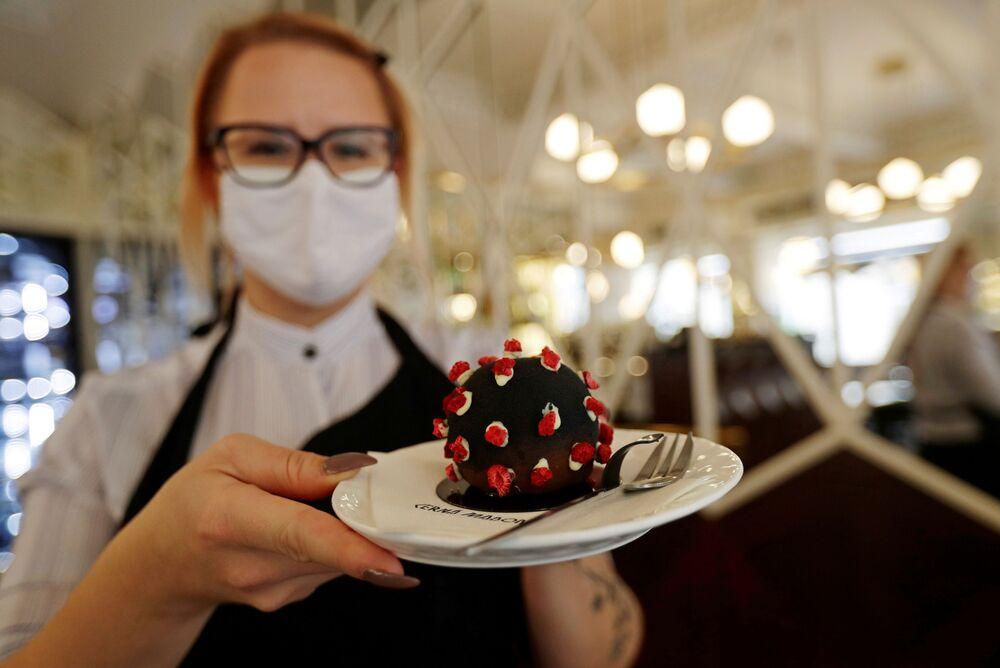 新型コロナウイルスSARS-CoV-2とかたどったケーキを提供する店員
