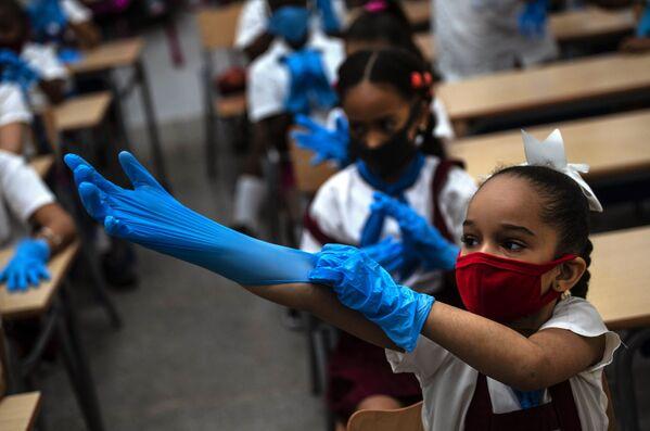 キューバ首都ハバナで11月2日、授業中に手袋をはめる女子児童 - Sputnik 日本