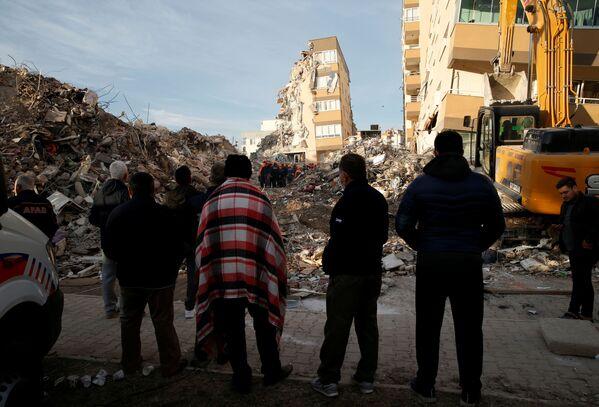 トルコ西部のイズミルで11月3日、建物の崩壊現場で行われる救助活動を見守る地元住民ら - Sputnik 日本