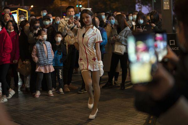 中国・北京でショッピング街で10月31日、看護師の格好をして通りを歩く女性  - Sputnik 日本