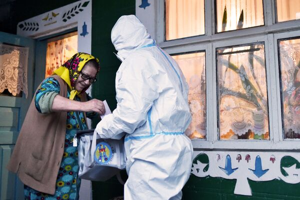モルドバの首都キシナウ近郊で11月1日、防護服姿で大統領選挙の投票箱を持って回る選挙管理委員 - Sputnik 日本
