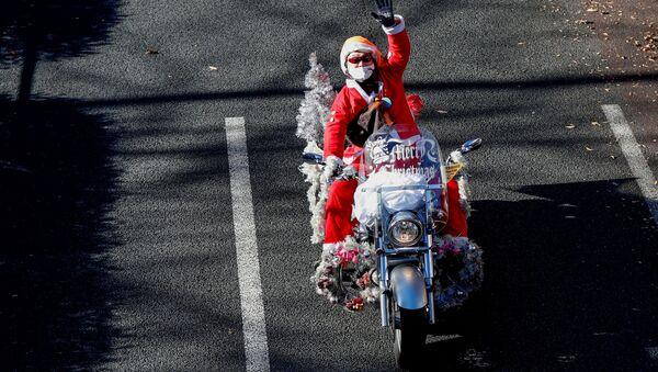 Мужчина в костюме Санта-Клауса на мотоцикле Harley Davidson во время рождественского парада в Токио - Sputnik 日本