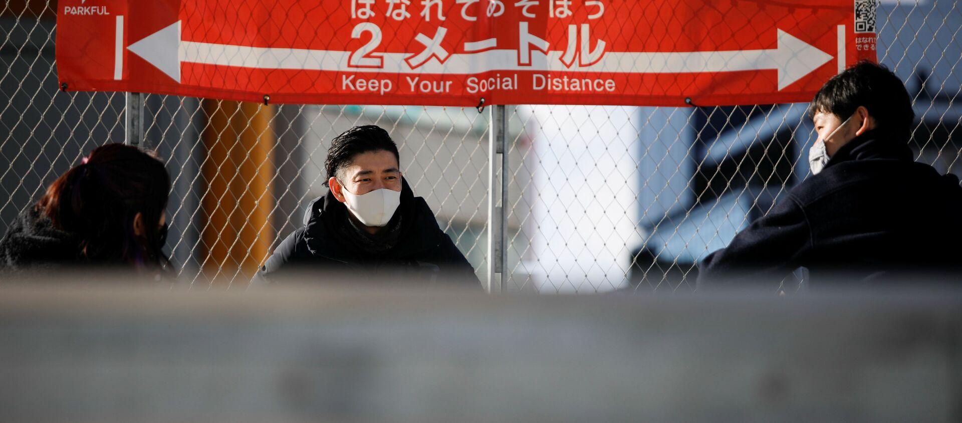Люди в масках на фоне плаката о необходимости соблюдения социальной дистанции в Токио - Sputnik 日本, 1920, 16.01.2021