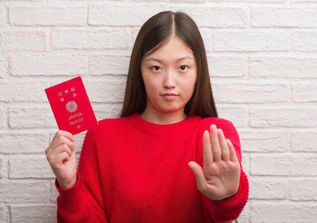日本のパスポートを持っている女性(アーカイブ写真)