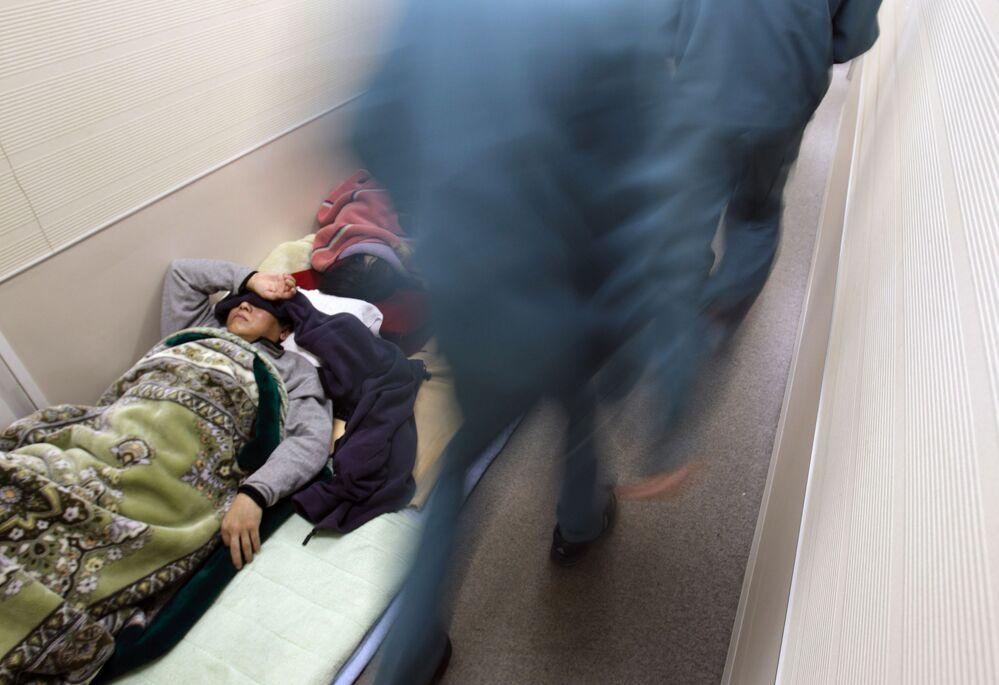 福島県郡山市で、避難区域の住民のための避難所の廊下で横になる男性(2011年3月16日撮影)