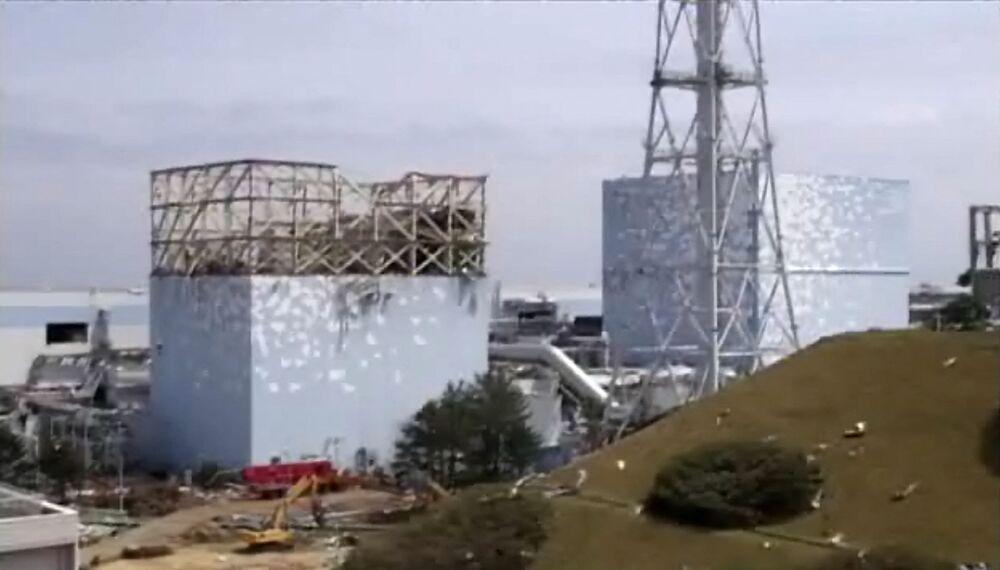 福島第一原発1号機(左)と2号機(右)の原子炉建屋(2011年5月6日撮影)