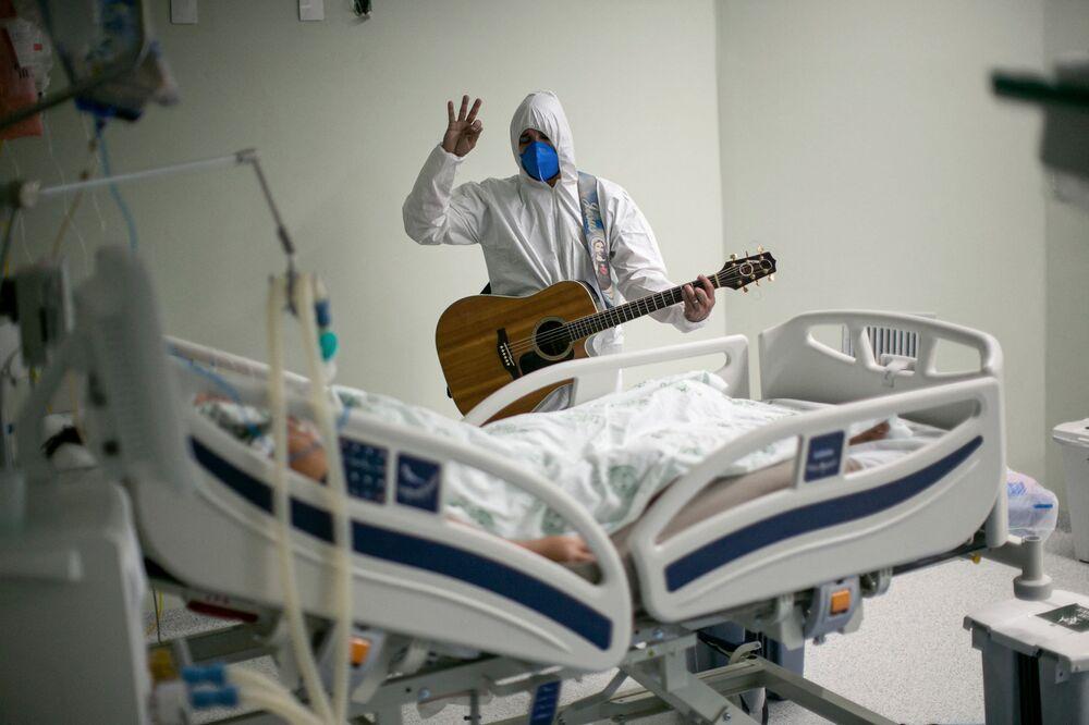 ブラジル・パラー州ベレンの慈善病院で、イースターのお祝いで新型コロナウイルス患者にギターの弾き語りをする医療従事者