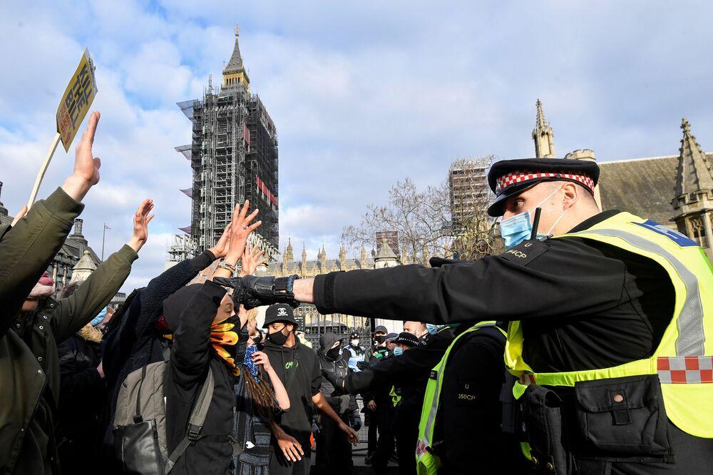 英ロンドンで行われた抗議デモで、警察に向かって手を挙げるデモ隊
