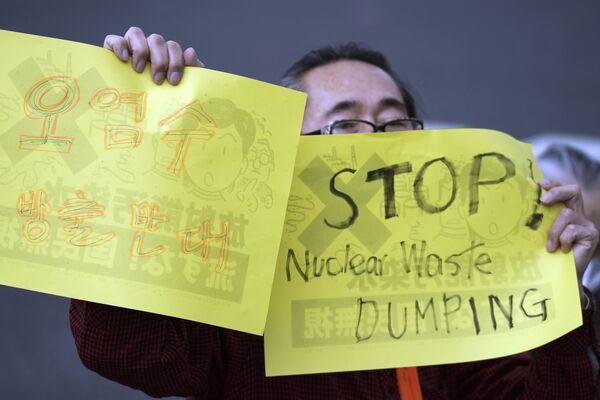福島第一原発の処理水の海洋放出が決定したことを受け、東京都千代田区の首相官邸前で行われた抗議デモで、プラカードを掲げる男性 - Sputnik 日本