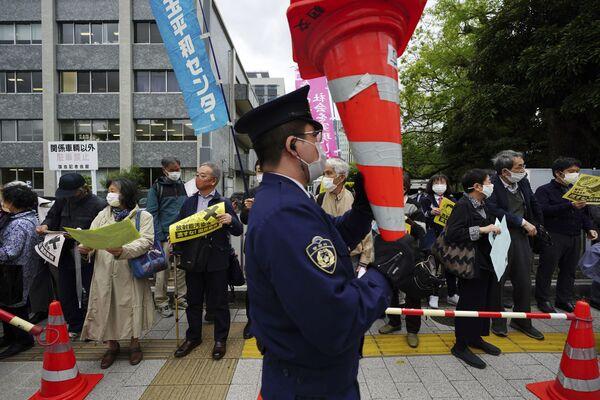 福島第一原発の処理水の海洋放出が決定したことを受け、東京都千代田区の首相官邸前で行われた抗議デモで、コーンを持ち上げる警察官 - Sputnik 日本