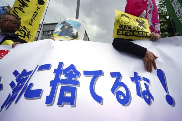 福島第一原発の処理水の海洋放出が決定したことを受け、東京都千代田区の首相官邸前で行われた抗議デモで「海に捨てるな」と書かれた横断幕を持つ人々 - Sputnik 日本