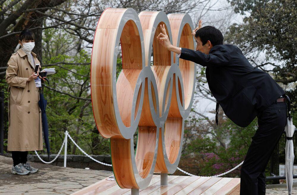 東京都八王子市の高尾山山頂に設置された五輪モニュメントのそばでポーズをとる男性