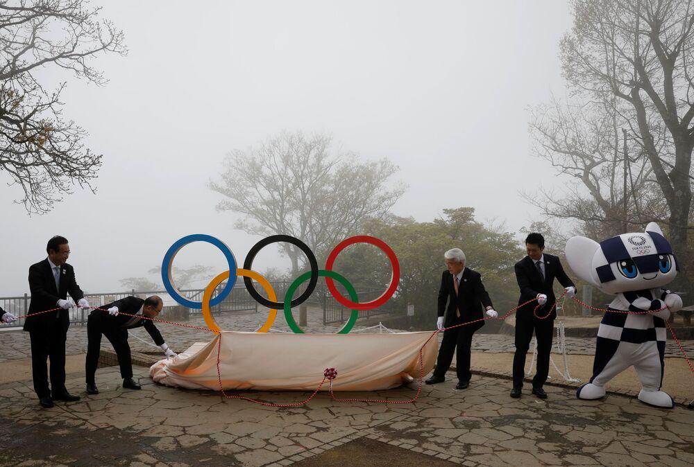 東京都八王子市の高尾山山頂に設置された五輪モニュメントの除幕を行う多羅尾光睦副都知事(左から2人目)と宮下純一氏(右)