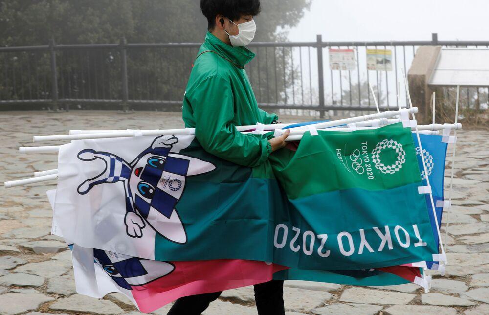 東京都八王子市の高尾山山頂で行われた五輪モニュメントの除幕式で、のぼりを運ぶスタッフ