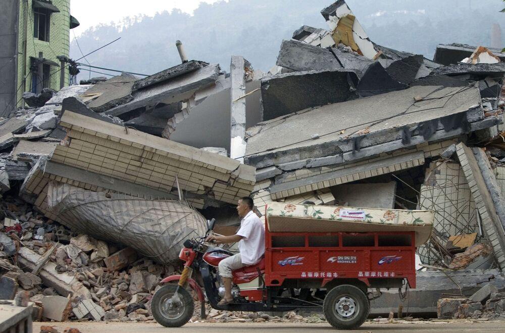 四川省漢旺で、地震で倒壊した建物の前をスクーターで通り過ぎる住民