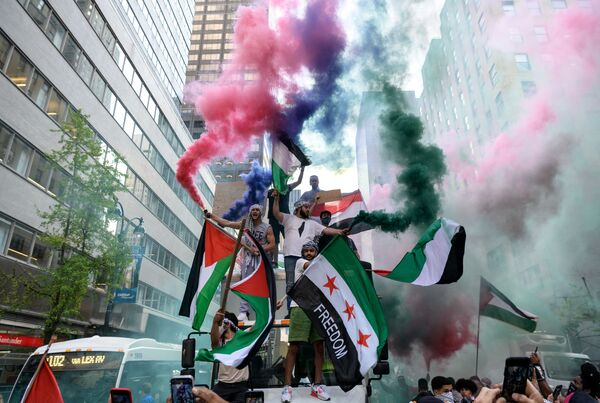 米ニューヨーク州マンハッタンのミッドタウンで、パレスチナとシリアの国旗を掲げて支援するデモ隊 - Sputnik 日本