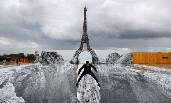 フランス・パリで、エッフェル塔前のトロカデロ広場に設置された巨大な絵画の上でポーズをとる男性 - Sputnik 日本