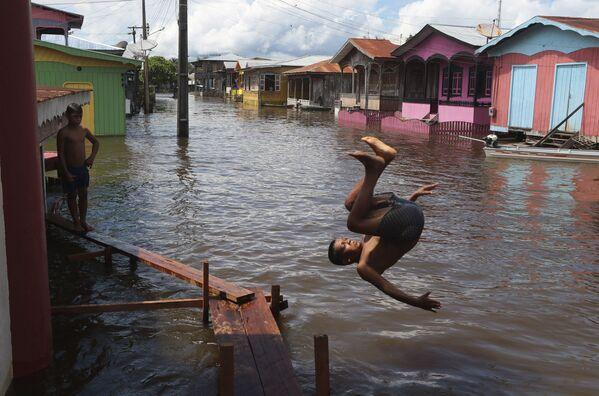 ブラジル・アマゾナス州で、大雨で冠水した道路に飛び込む少年 - Sputnik 日本