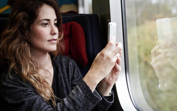 車窓の風景を撮影する女性  - Sputnik 日本