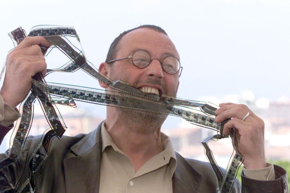 第51回映画祭で、エメリッヒ監督の映画『GODZILLA』の フォトコールでフィルムを噛むフランスの俳優ジャン・レノ氏(1998年)