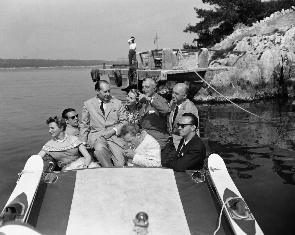 第9回映画祭で、昼食会の後ボートで出発するイタリアの映画監督ロベルト・ロッセリーニ氏と妻で女優イングリッド・バーグマン(中央)(1956年5月9日)