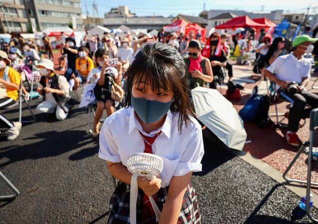 東京・品川区のしながわ中央公園で、聖火ランナーの控えランナーらが聖火を受け渡すイベント「トーチキス」を見る生徒