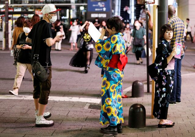 浴衣を着て街を店の宣伝をする女性
