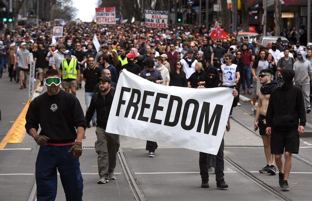 オーストラリア・メルボルンで行われたロックダウン反対デモで、スローガンを掲げて通りを行進するデモ参加者