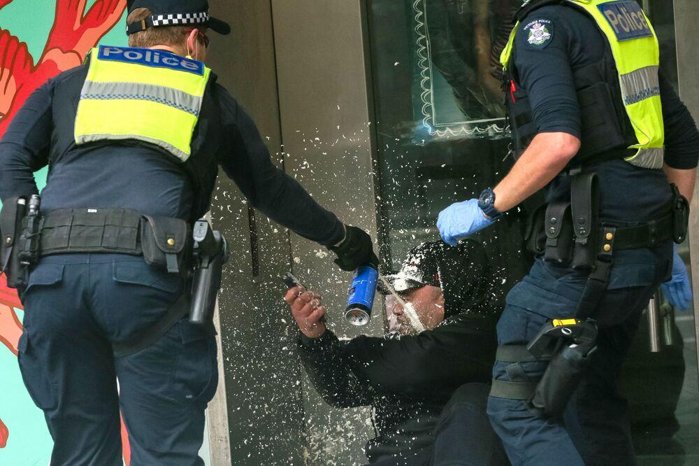 オーストラリア・メルボルンで行われたロックダウン反対デモで、デモ参加者に唐辛子スプレーをかける警察