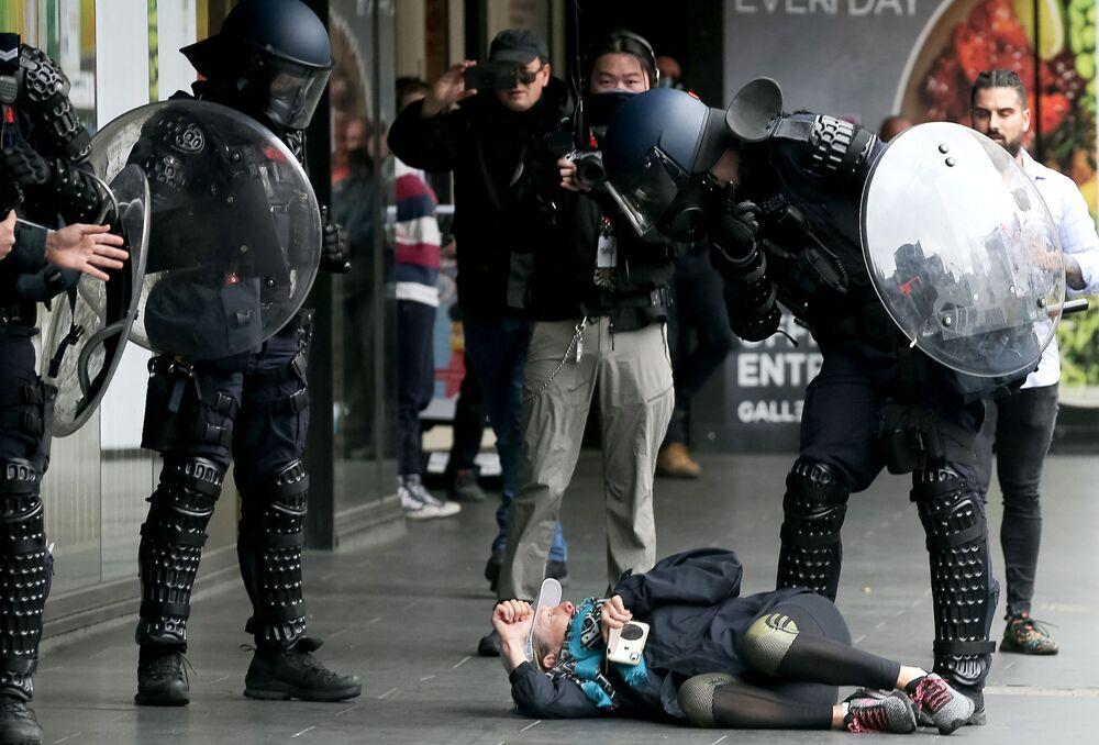 オーストラリア・メルボルンで行われたロックダウン反対デモで、デモ参加者を拘束する機動隊