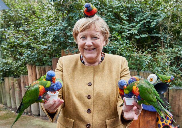 ドイツ・マルローにあるバードパークでヒインコに餌をあげながらポーズをとるアンゲラ・メルケル首相