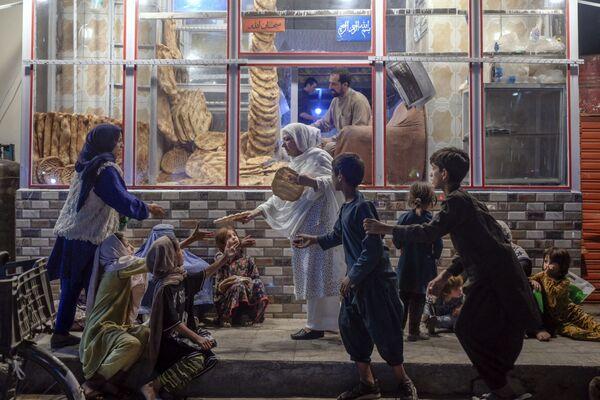 アフガニスタン・カブールで、パン屋の前で子どもたちにパンを分ける女性 - Sputnik 日本