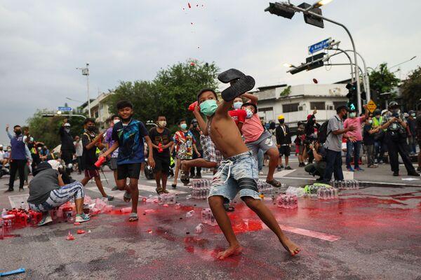 タイ・バンコクで行われた反政府デモで、赤いペンキが入ったボトルを警察に投げつける若者ら - Sputnik 日本