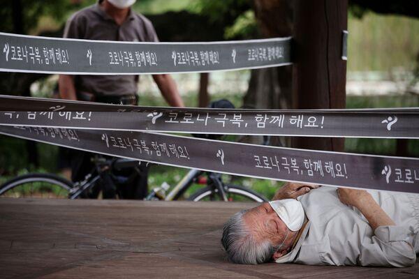 韓国・ソウルで、新型コロナウイルスの感染対策で封鎖された公園で寝そべる男性 - Sputnik 日本