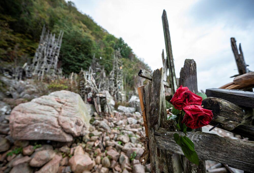 芸術家のラルス・ヴィルクス氏が制作した木製の彫刻「Nimis」に置かれた花