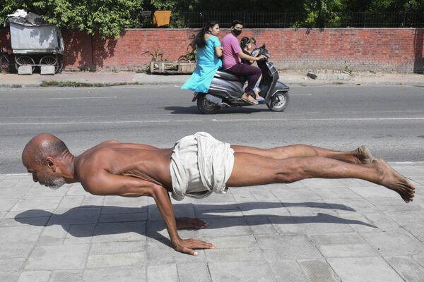 インド・パンジャーブ州アムリトサルで、路上でヨガのポーズをとる男性 - Sputnik 日本