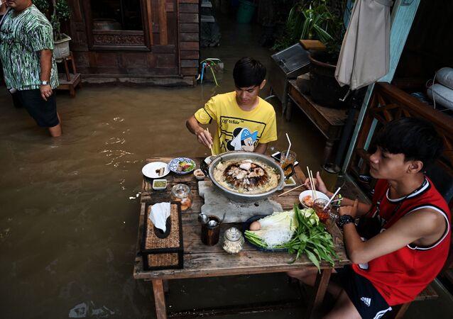 タイ中部・ノンタブリー県で、水浸しになったレストラン「Chaopraya Antique」で食事をする人々