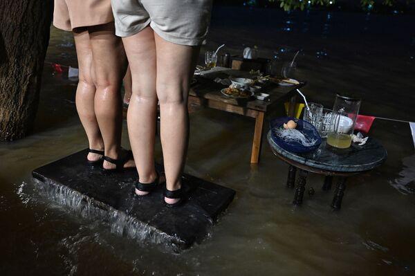 タイ中部・ノンタブリー県で、水浸しになったレストラン「Chaopraya Antique」で椅子に立ちながら食事をする人々 - Sputnik 日本