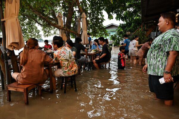 タイ中部・ノンタブリー県で、水浸しになったレストラン「Chaopraya Antique」で食事をする人々 - Sputnik 日本