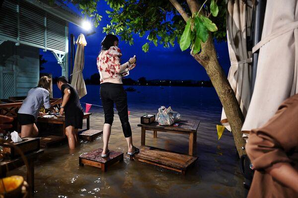タイ中部・ノンタブリー県で、水浸しになったレストラン「Chaopraya Antique」で椅子の上に立つ女性 - Sputnik 日本