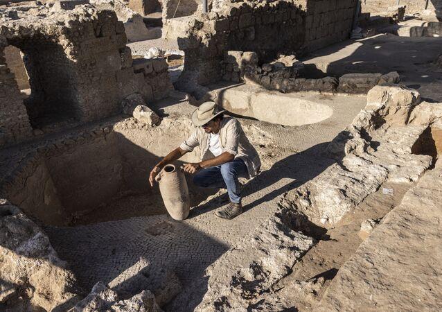 イスラエル・ヤブネで発見されたワイナリーの遺跡で、壺を調べる考古学者
