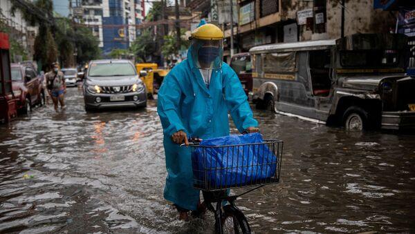 Мужчина в маске едет на велосипеде по затопленной улице в Маниле, Филиппины - Sputnik 日本