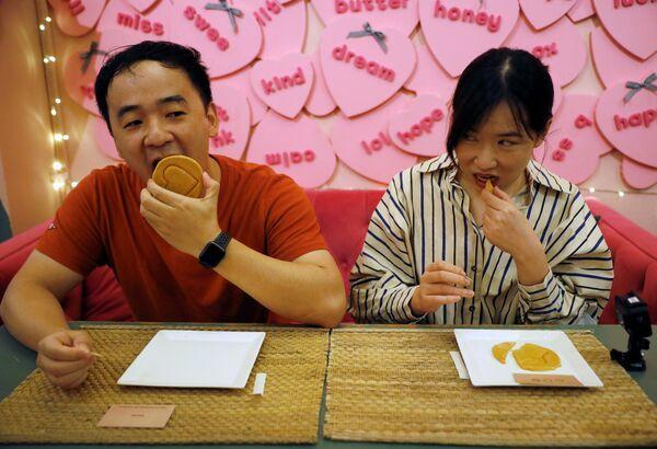シンガポールのカフェで、『イカゲーム』劇中で行われた「ダルゴナ(カルメ焼き)」の型抜きにチャレンジする男女 - Sputnik 日本