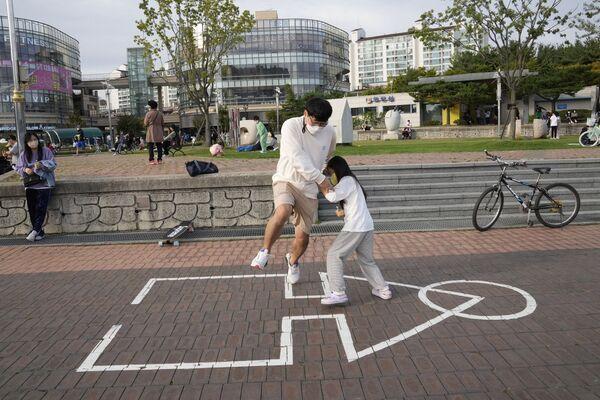 韓国・京畿道高陽(コヤン)市の公園で、『イカゲーム』劇中で行われたゲーム「イカゲーム」を遊ぶ親子 - Sputnik 日本