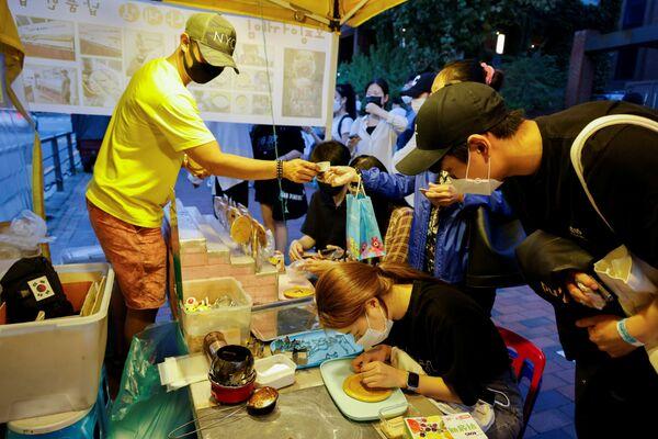 韓国・ソウルで、「イカゲーム」の『イカゲーム』に登場するお菓子「ダルゴナ(カルメ焼き)」を売る屋台 - Sputnik 日本