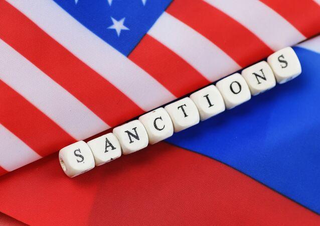 Надпись санкции, сложенная из кубиков между флагами США и России