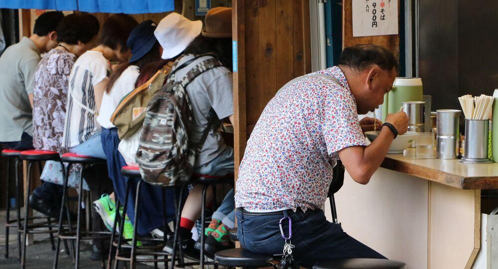 東京、ラーメンを食べいている日本人