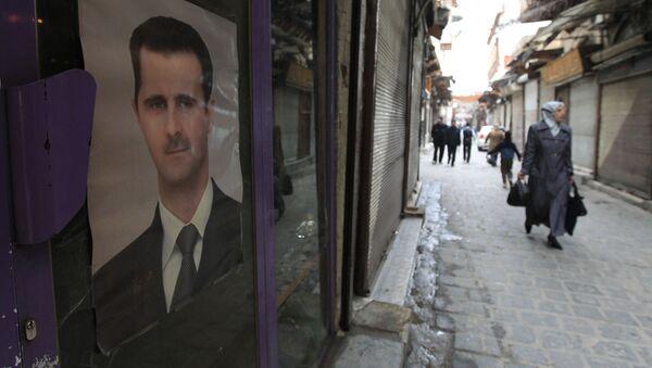 Жительница Дамаска проходит мимо здания с портретом президента Сирии Башара Асада - Sputnik 日本